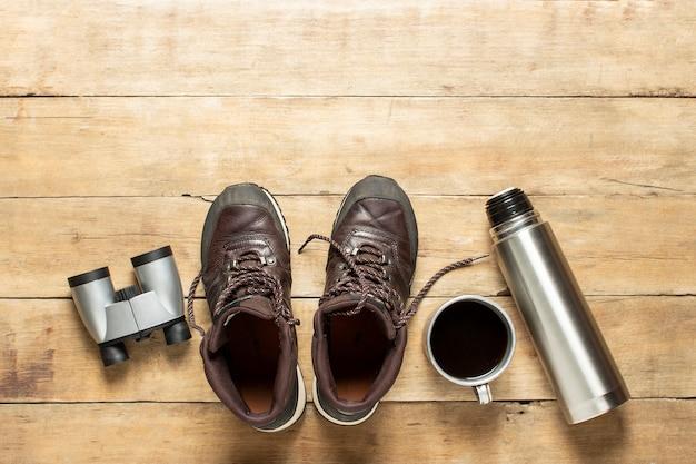 Stiefel für spur, fernglas, thermoskanne, tasse mit tee auf hölzernem hintergrund. konzept von wandern, tourismus, camp, bergen, wald.