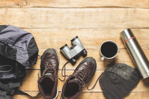 Stiefel für trail, fernglas, trekkingzubehör auf hölzernem hintergrund. das konzept von wandern, tourismus, camp, bergen, wald. banner. flache lage, draufsicht