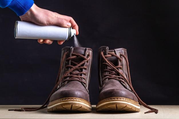 Stiefel reinigen und geruchsbeseitigung mit spray schmutzige stiefel mit unangenehmem geruch. verschwitzte schuhe nach langen spaziergängen und aktivem lebensstil. schuhpflege