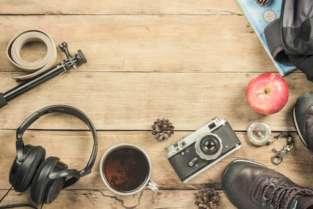 Stiefel, rucksack, kompass und andere campingausrüstung auf einer holzoberfläche. das konzept des wanderns in den bergen oder im wald, tourismus, zeltruhe, lager. flachgelegt, draufsicht.