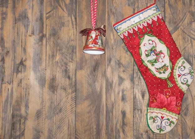 Stiefel und eine glocke, die am hölzernen hintergrund hängt. weihnachtsdekorationen