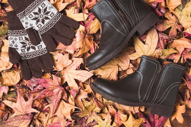 Stiefel und handschuhe auf trockenem blatthintergrund
