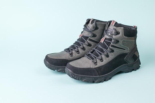 Stiefel zum wandern bei kaltem wetter auf blauem grund. herrenschuhe für kaltes wetter. lässige sport herrenschuhe.