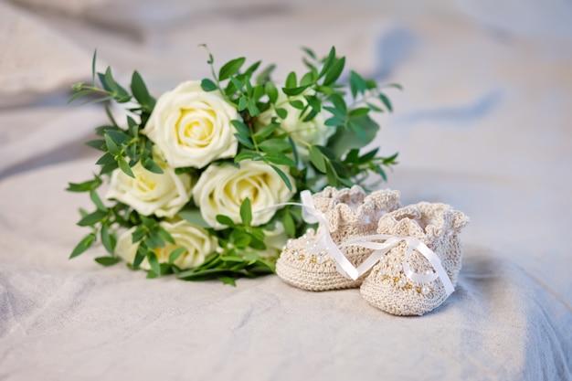 Stiefeletten und blumen des kleinen babys auf einem durchbrochenen leinenplaid. warten auf baby-girl. schwangerschaft, mutterschaft.