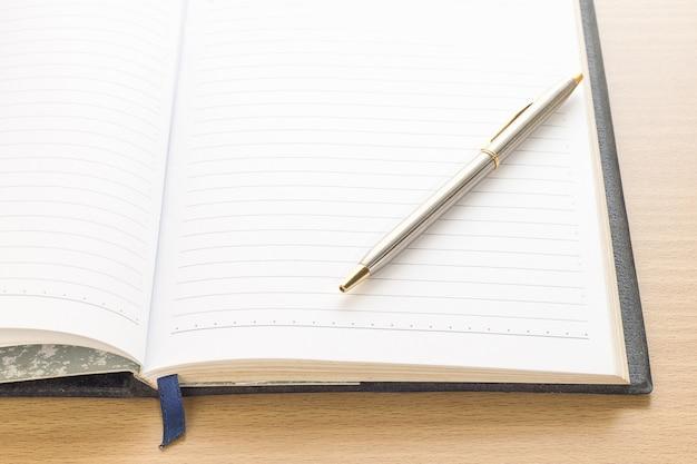 Stift auf leere notizseite des notizbuches setzen