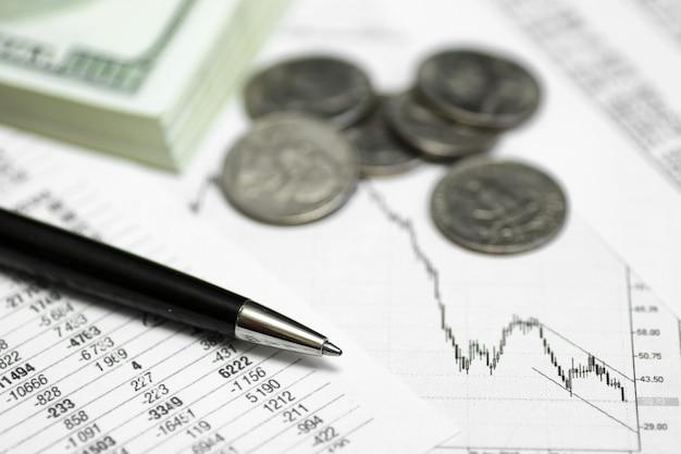 Stift auf papier mit den kursnotierungen und diagrammen der dynamik ihres wechselgelds und der münzen