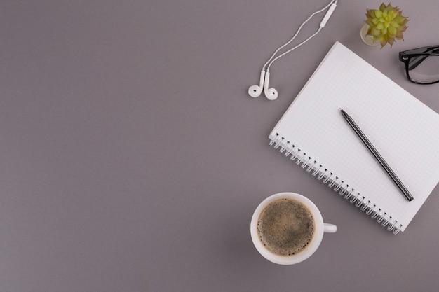 Stift in der nähe von notizblock, tasse, ohrhörer und brille