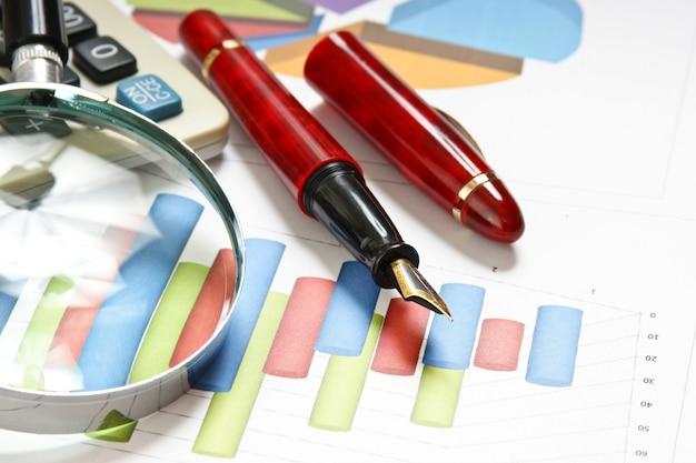 Stift, lupe und das arbeitspapier mit einem diagramm