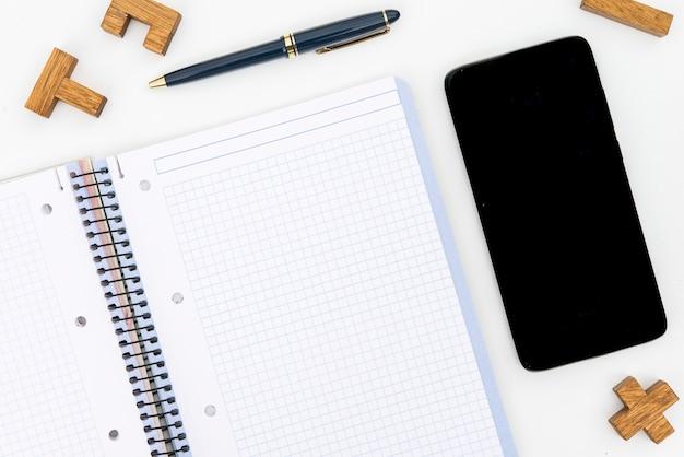 Stift, notizblock und handy mit hölzernen puzzleteilen