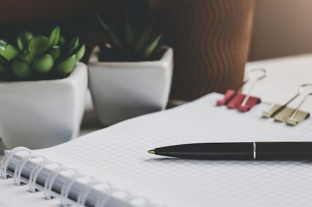 Stift, notizbuch, topfpflanzensucculents auf dem tisch. arbeitsplatz