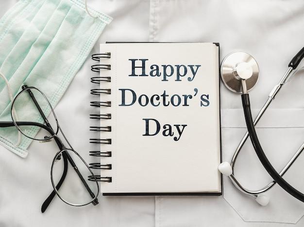 Stift, stethoskop, gesichtsmaske und brille liegen auf einem medizinischen kleid. glücklicher tag des doktors. nahaufnahme, keine leute. herzlichen glückwunsch an verwandte, freunde und kollegen