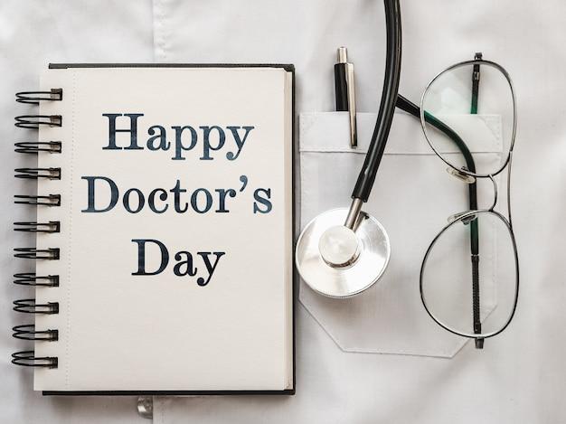 Stift, stethoskop, gesichtsmaske und brille liegen auf einem medizinischen kleid. glücklicher tag des doktors. nahaufnahme, keine leute.