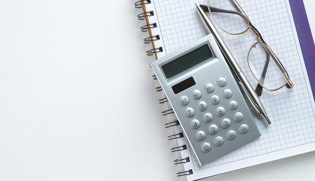 Stift, taschenrechner und brille auf einem offenen notizblock.