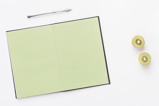 Stift über der oberseite eines offenen notizbuches mit der halbierten kiwi lokalisiert auf weißem hintergrund