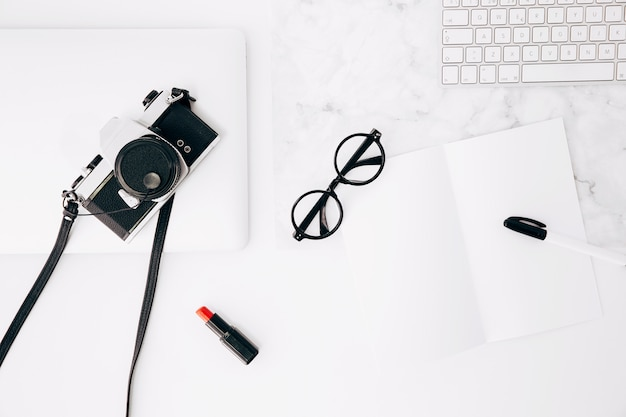 Stift und brille auf papier; roter lippenstift; kamera; tastatur und digitales tablet auf dem schreibtisch