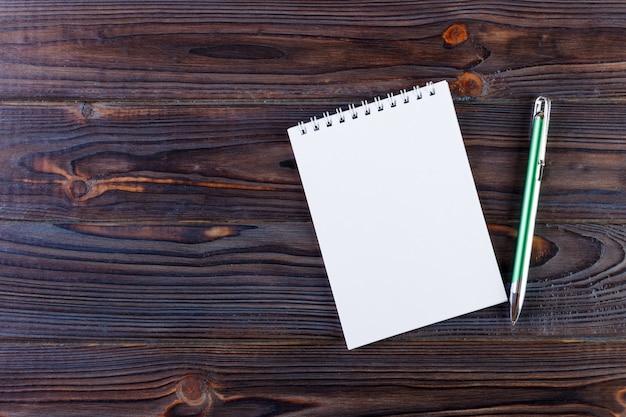 Stift und notizblock auf dem hölzernen schreibtisch