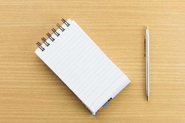 Stift und notizblock mit leerer seite