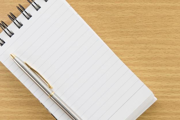 Stift und notizblock mit leerseite