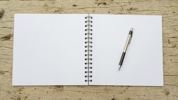 Stift und notizbuch auf holz.