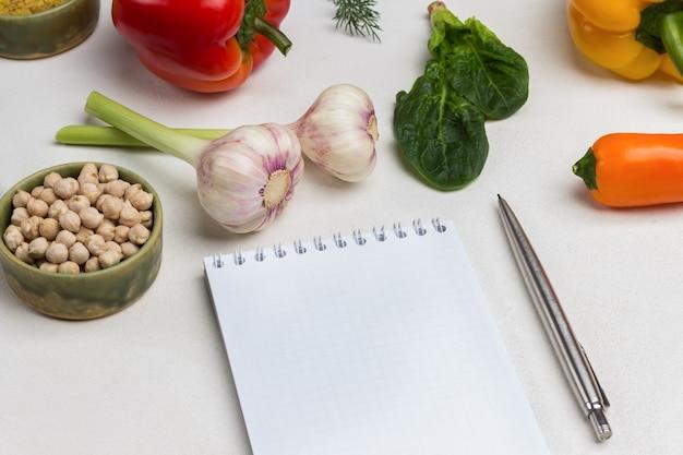 Stift und notizbuch. bulgur in der schüssel. knoblauch, pfeffer und spinatblätter auf dem tisch. weißer hintergrund. ansicht von oben