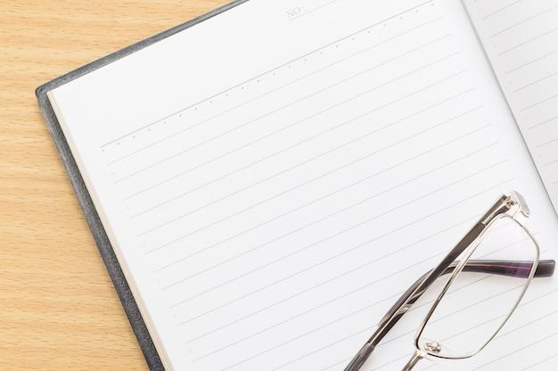 Stift und offenes notizbuch mit leerseite