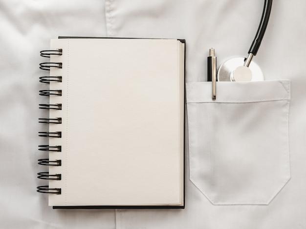 Stift und stethoskop liegen auf einem medizinischen kleid. glücklicher tag des doktors. nahaufnahme, keine leute. herzlichen glückwunsch an verwandte, freunde und kollegen
