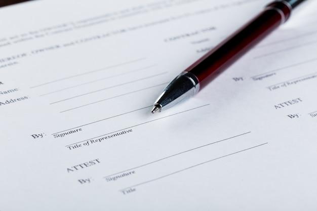 Stift- und vertragspapiere auf hölzernem schreibtisch