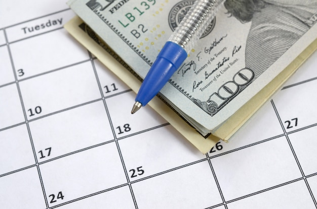 Stift und viele hundert us-dollar-scheine auf kalenderseite schließen