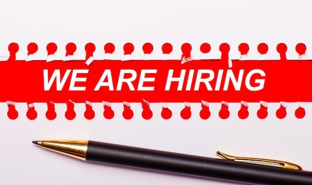 Stift und weißer, zerrissener papierstreifen auf leuchtend rotem hintergrund mit dem text we are hiring