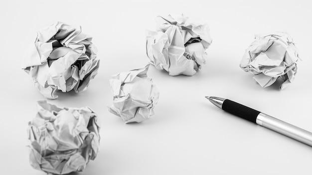 Stift und zerknitterte papierkugel auf einer weißen tabelle. - arbeits- und geschäftsideenkonzept.