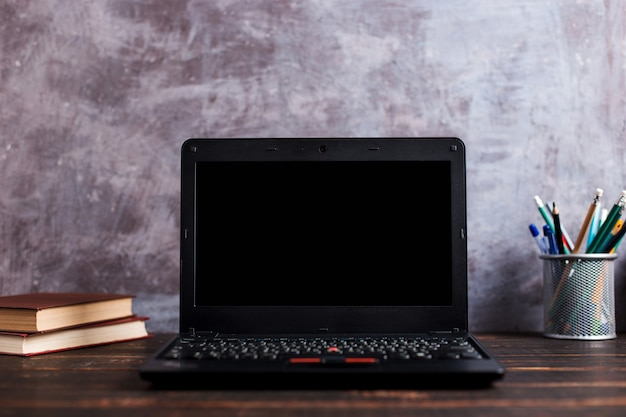 Stifte, apfel, bleistifte, bücher, laptop und gläser auf dem tisch, auf tafelhintergrund