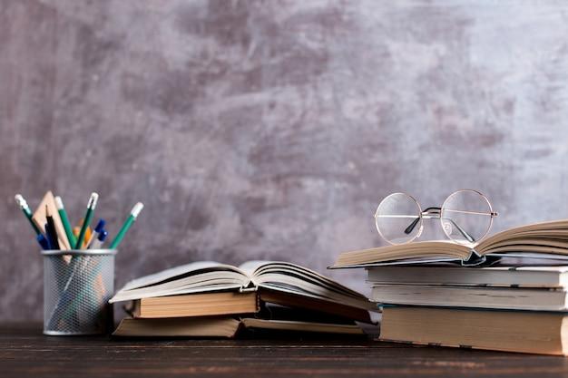 Stifte, apfel, bleistifte, bücher und gläser auf dem tisch