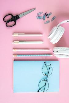 Stifte, bleistifte, clips, scheren, kopfhörer, brillen und notizbuch in blauem umschlag auf rosa hintergrund