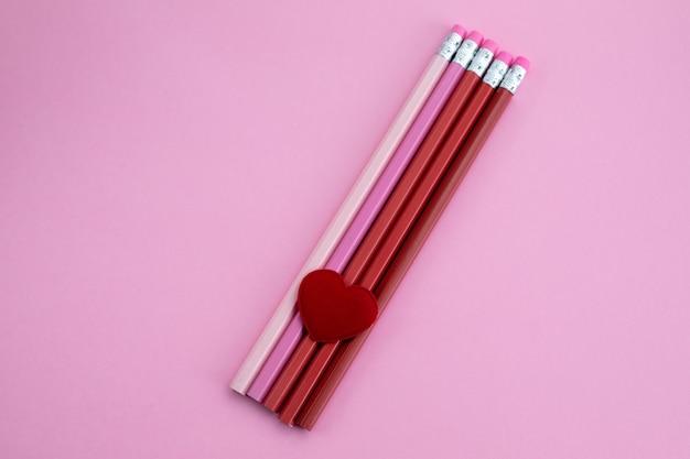 Stifte mit herz auf rosa hintergrund