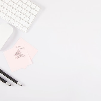 Stifte und haftnotizen in der nähe von tastatur und maus