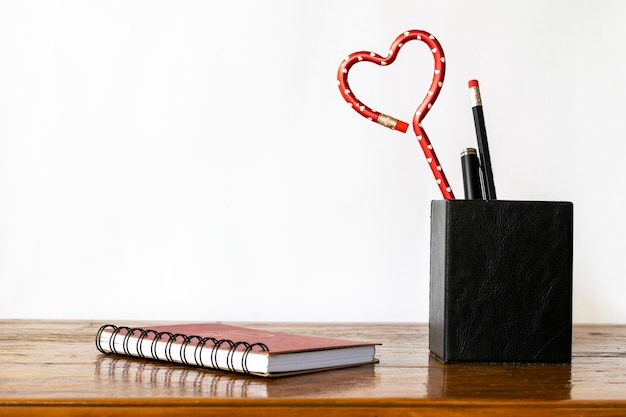 Stifthalter mit herzförmigem bleistift auf dem tisch, mit spiralblock.