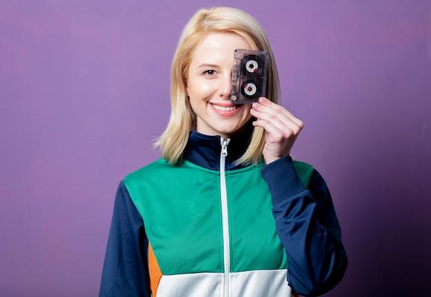Stil blonde frau in 80er jahren kleidung mit band kassette