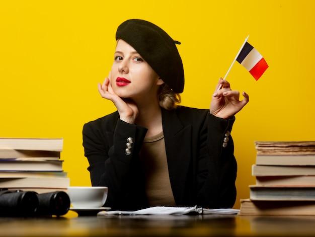 Stil blonde frau in baskenmütze mit französischer flagge und bücher herum auf gelb