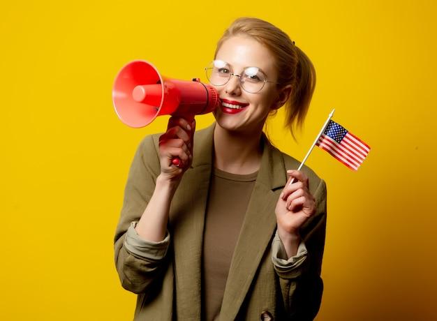 Stil blonde frau in jacke mit flagge der usa und megaphon auf gelb