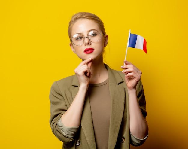 Stil blonde frau in jacke mit französischer flagge auf gelb