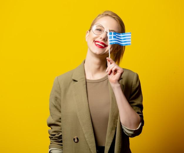Stil blonde frau in jacke mit griechischer flagge auf gelb