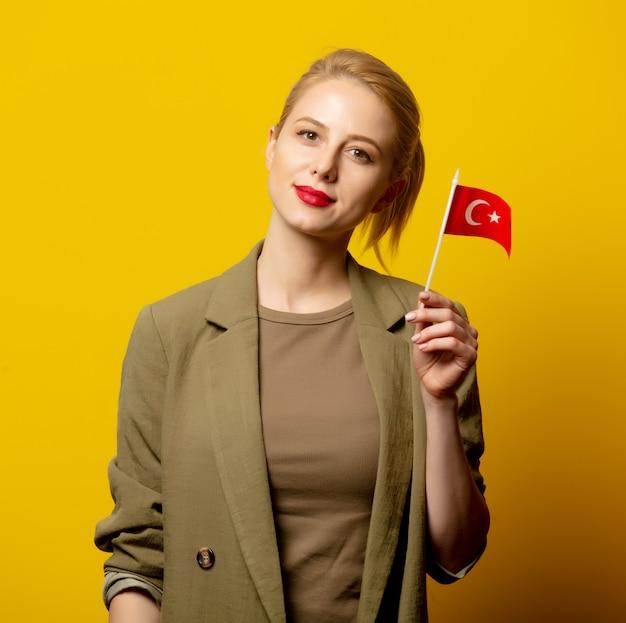 Stil blonde frau in jacke mit türkischer flagge auf gelb