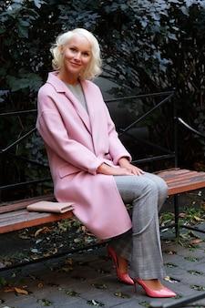 Stil blonde frau sitzt auf der bank, herbsttag.