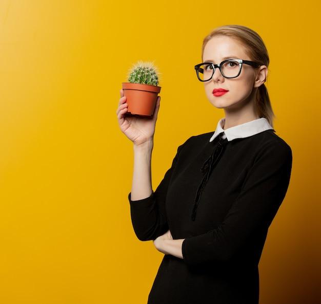 Stil frau in der schwarzen formellen kleidung mit kaktus