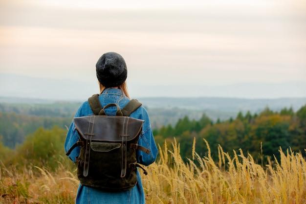 Stil frau in jeansjacke und hut mit rucksack in der landschaft mit bergen