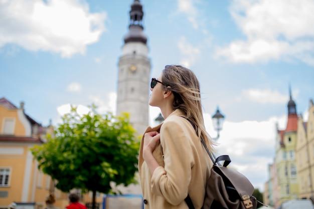Stil frau in sonnenbrille und rucksack in alten stadtzentrum platz. polen