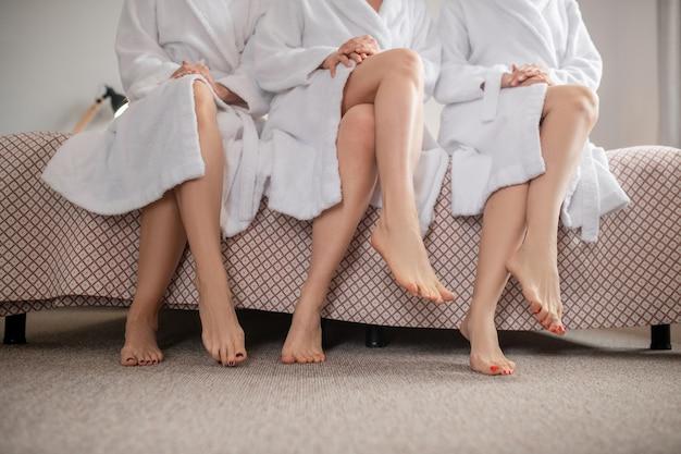 Stil. gepflegte nackte füße mit pediküre berühren den boden von frauen, die in gleichen positionen auf dem bett sitzen und ihre freizeit im spa verbringen, ohne gesicht