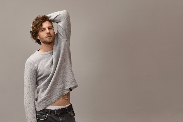 Stil, herrenbekleidung und modernes modekonzept. horizontale ansicht des attraktiven selbstbewussten jungen unrasierten kerls in den jeans, die hand hebend, hält es hinter kopf, zeigt tätowierung auf bauch und weißer unterwäsche