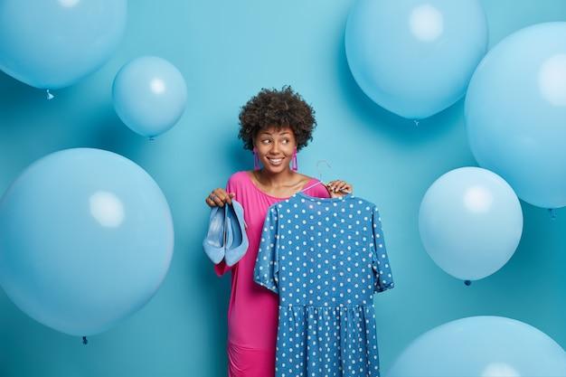 Stil, kleidungskonzept. modische frau kauft outfit für besondere anlässe, wartet auf party, hält ausgefallene tupfenkleider auf kleiderbügeln und blaue schuhe mit hohen absätzen, umgeben von großen aufgeblasenen luftballons