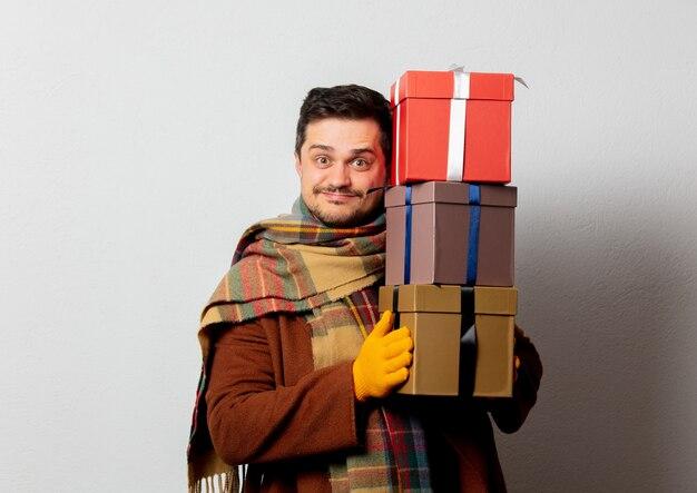Stil mann in mantel und schal mit geschenkboxen
